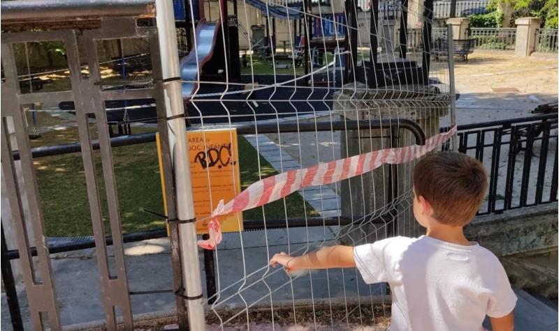Un xiquet espera a poder jugar de nou en el parc./ Jordi Ferri