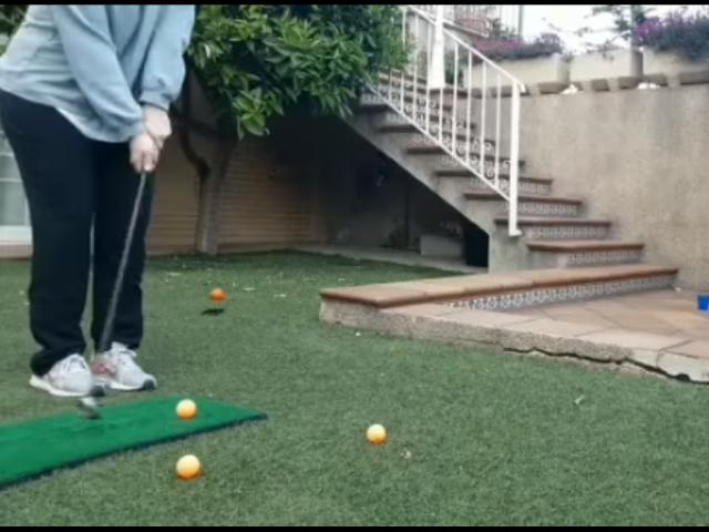 Una jove jugant a golf en sa casa durant el confinament.