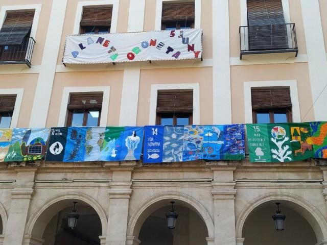 La gran pancarta penja dels balcons de la Plaça de Dins.