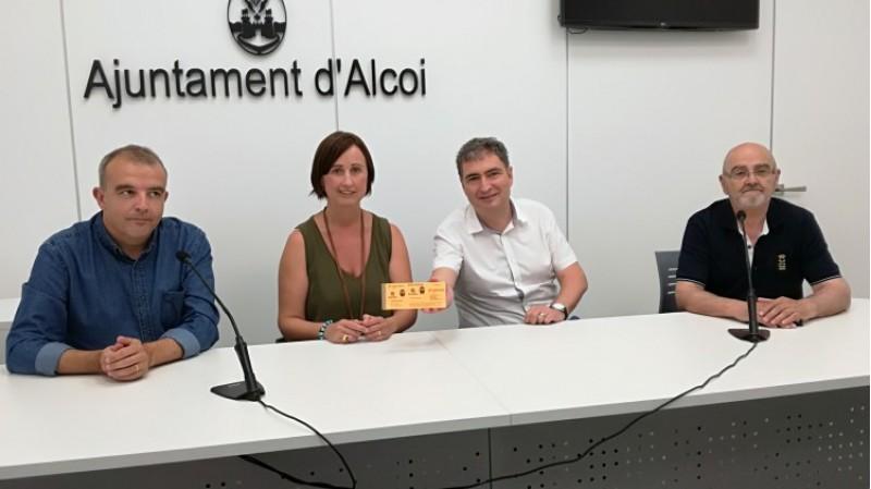 Exequiel Moltó, de Vectalia (Tuasa), mostra els abonaments. A l'esquerra els regidors de mobilitat i benestar social, Jordi Martínez i Aroa Mira. A la dreta, el director de l'Economat de Càritas Alcoi, Rafael Tortosa