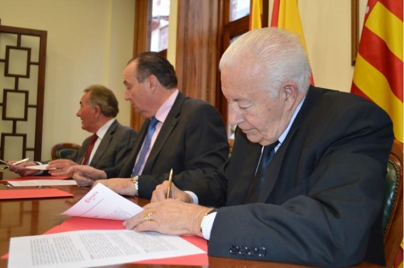 Enrique Rico, en primer pla, signa el conveni / R. Lledó